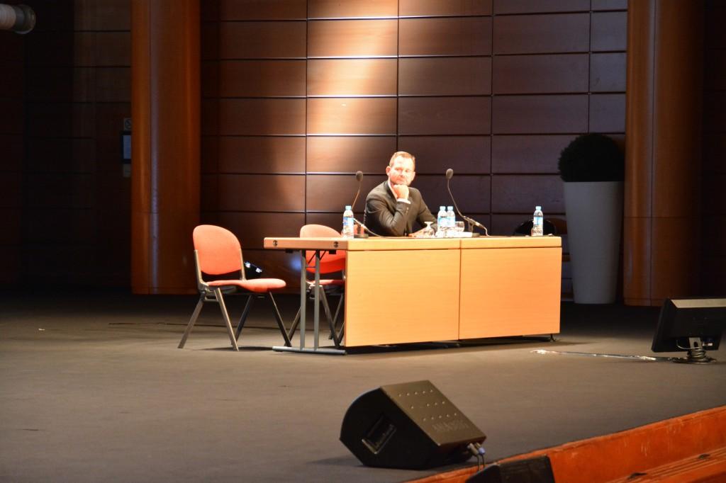 Gildas Illien sitz am Tisch auf der Bühne bei einer Session in der IFLA 2014